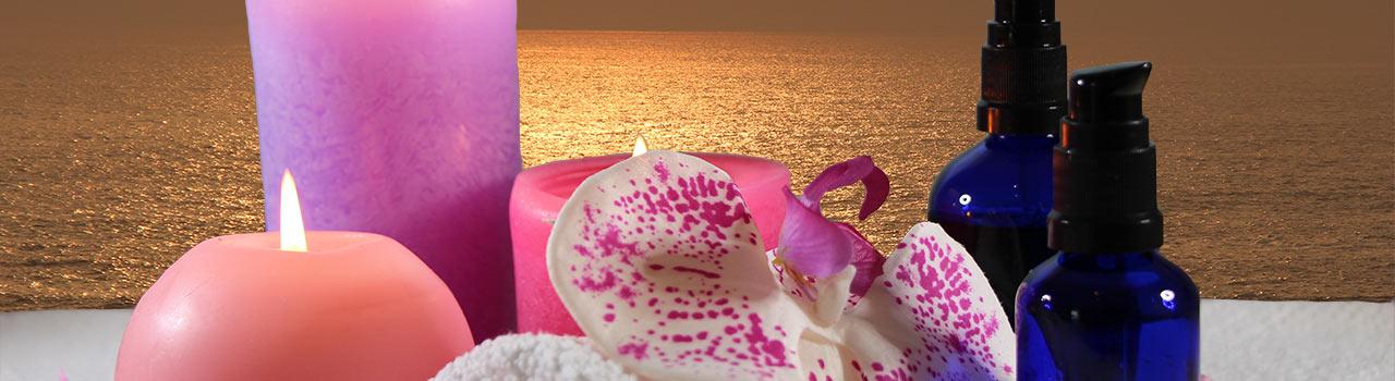 Bild von zwei Kerzen, einer Blume, zwei Ölflaschen und einem kleinen Handtuch, die die japanischen Massagen symbolisieren. Die japanischen Massagen gehören zu den Leistungen, die in der Praxis der Heilpraktikerin Diane Zardini in Garmisch-Partenkirchen angeboten werden.