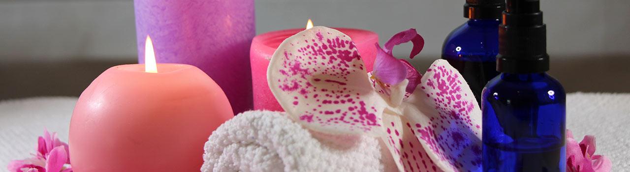 Bild von zwei Kerzen, Blumen, zwei Ölflaschen und einem kleinen Handtuch, die die japanischen Massagen symbolisieren. Die japanischen Massagen gehören zu den Leistungen, die in der Praxis der Heilpraktikerin Diane Zardini in Garmisch-Partenkirchen angeboten werden. Sechstes Bild das sich oben auf der Startseite befindenden Diashow.